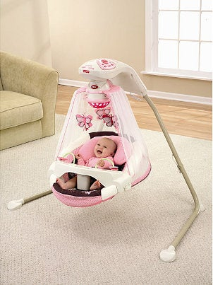 Cute baby girl in a baby swing