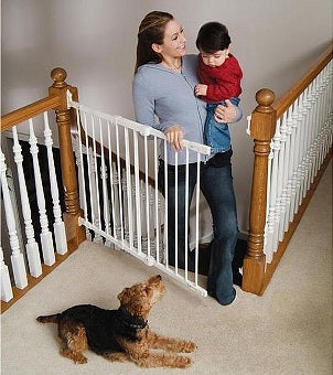 Mom carrying baby through a stairway safety gate