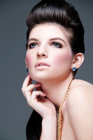 An elegant model wearing gold chains and blue gemstone earrings