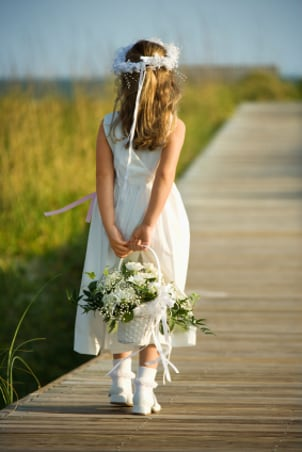 Cute flowergirl wearing a white dress and shoes at a wedding