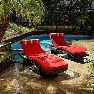 Chaise lounges next to a backyard pool