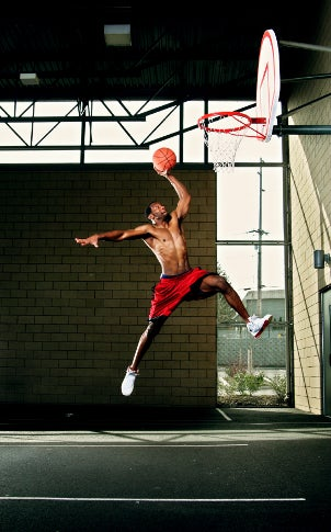 Man wearing basketball shoes, slam dunking a basketball