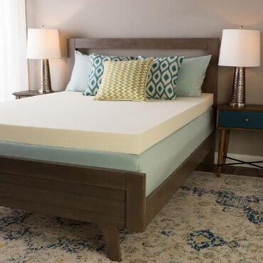Memory foam mattress topper on bed
