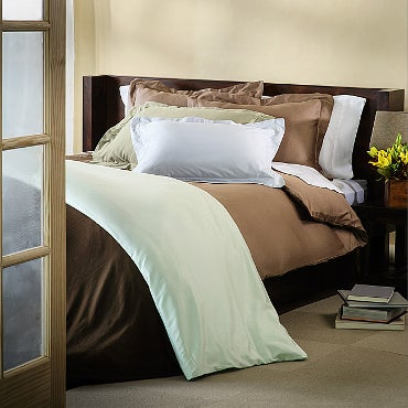 Unmade bed with brown, white, and mint bedding