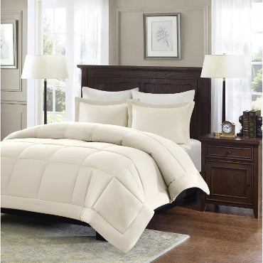Beige comforter set on dark bed