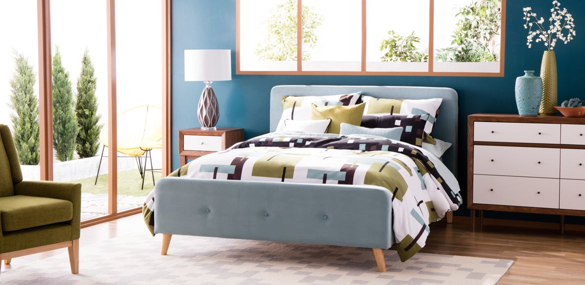 A Mid-Century Modern styled bedroom with shades of blue, greens, and browns with tapered legs and retro prints