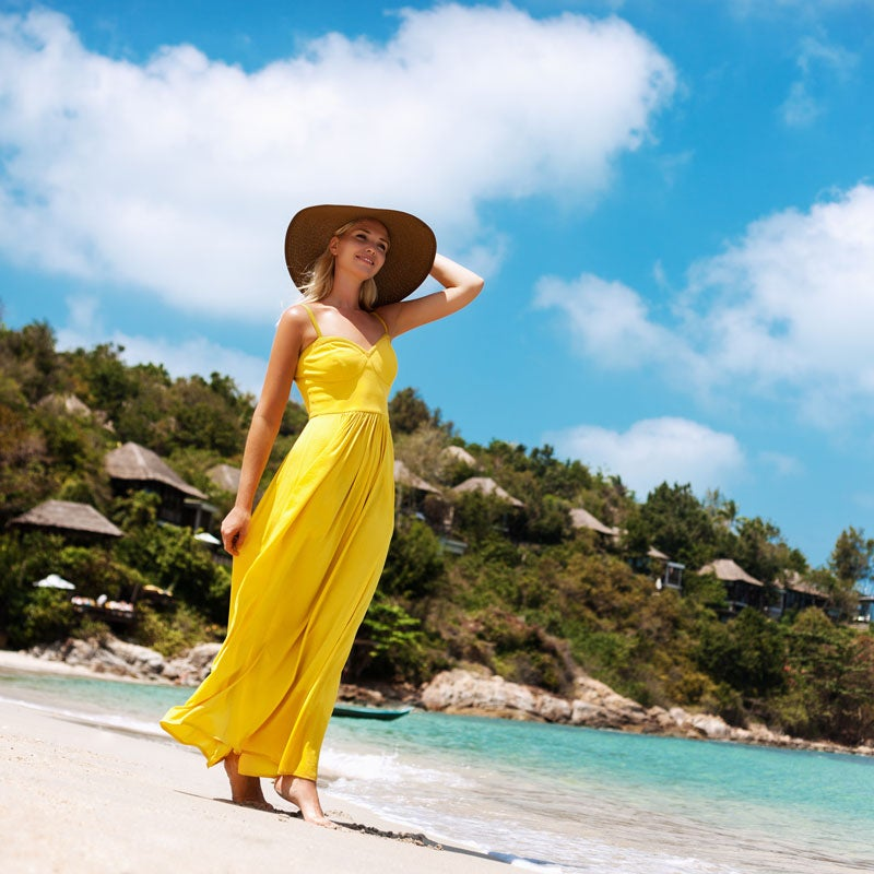 woman in sun hat and yellow maxi dress walks on the beach