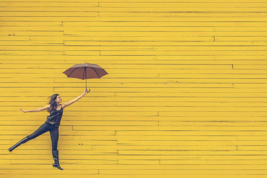 Picture of a woman with an umbrella jumping against a bright yellow background