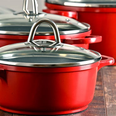 Red carbon steel cookware with glass lid on wooden table
