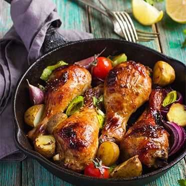 Cast-iron skillet filled with roasted chicken and vegetables sitting on rustic blue table