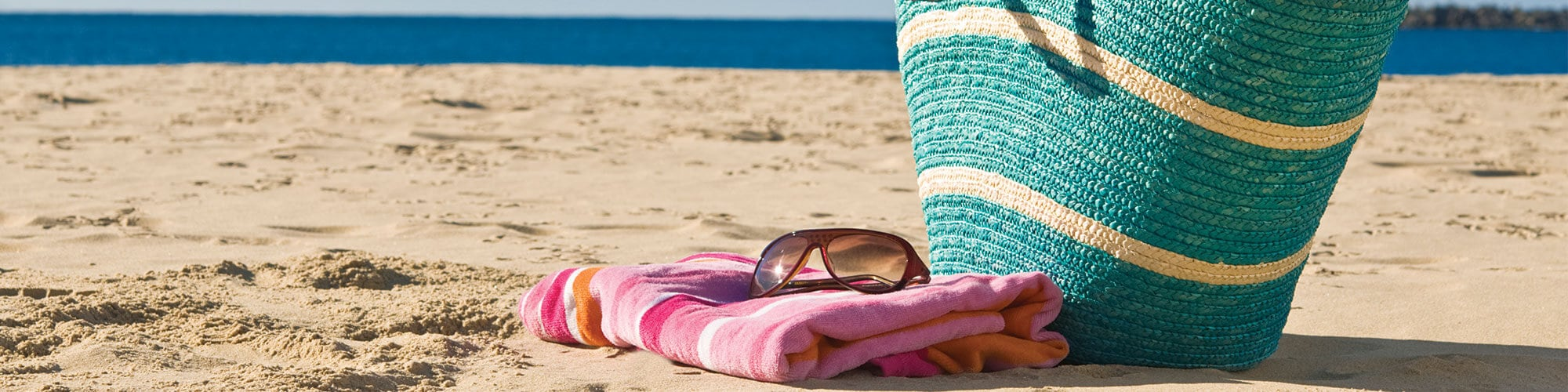 Blue striped beach tote with sunglasses, a towel, straw sun hat, and sandals on the beach