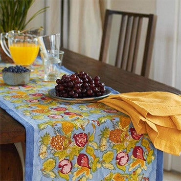 A floral print table runner on table with juice and grapes