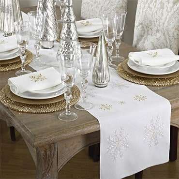 A snowflake embellished table runner on holiday-themed table
