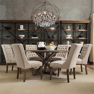 Round table with tufted, upholstered chairs in nicely furnished dining room.