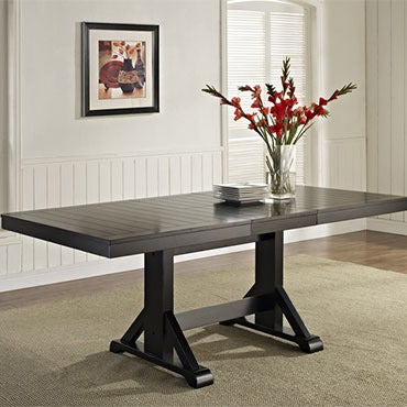 Dark brown trestle table in white dining room.