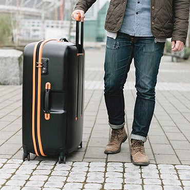 Man walking on sidewalk with large black and orange suitcase