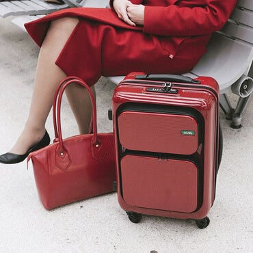 Woman in red coat waiting at an airport with her red carry-on bag and red handbag.