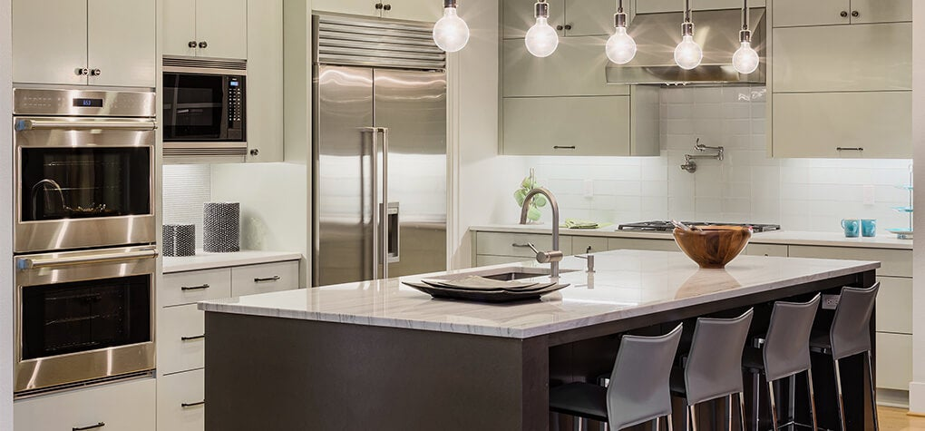 Large kitchen with stainless steel appliances, and large kitchen island