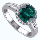 White gold ring with round emerald with a halo of diamonds