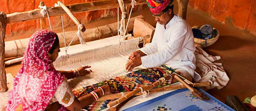 Two people from India weaving a rug on a loom