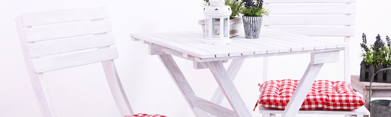 White bistro table with red buffalo check chair cushions