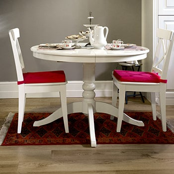 White dining table with red chair cushions.