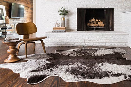 Living room with fireplace and animal hide area rug