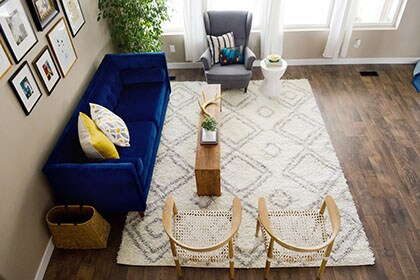 Living room with area rug and bright blue couch