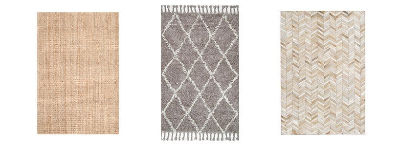 Three neutral colored rugs incluing a jute rug, hand woven trellis rug, and chevron cow hide leather rug