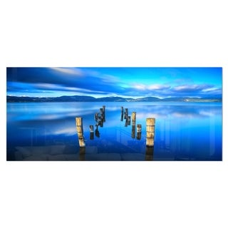 Designart 'Wooden Pier Remains in Blue Sea' Seascape Photo Metal Wall Art