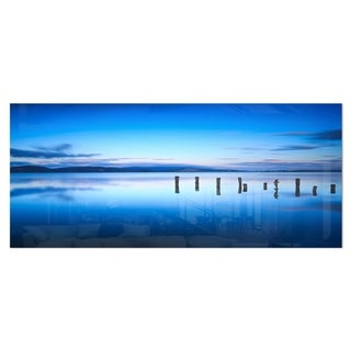 Designart 'Jetty Remains in Blue Sea' Seascape Photo Metal Wall Art