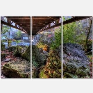 Designart - Large Rocks Under Bridge in Creek - Landscape Photo Glossy Metal Wall Art
