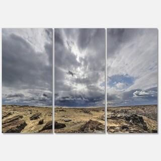 Designart - Sky and Stones under Dark Clouds - Landscape Glossy Metal Wall Art