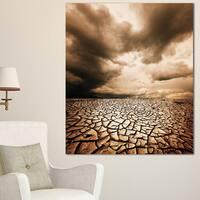 Designart 'Cracked Drought Land with Dark Clouds' Oversized Landscape Canvas Art - Brown
