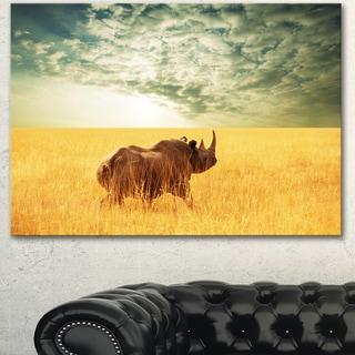 Designart 'Rhino in Grassland under Cloudy Sky' African Canvas Artwork