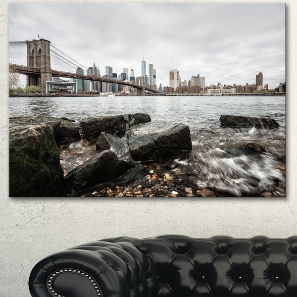 Designart 'Brooklyn Bridge with Rocks on Shore' Large Cityscape Artwork on Canvas