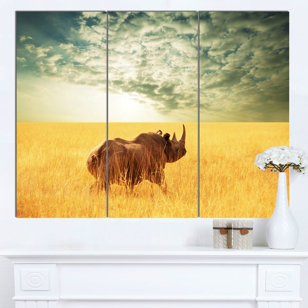 Designart 'Rhino in Grassland under Cloudy Sky' African Canvas Artwork - Brown/Blue