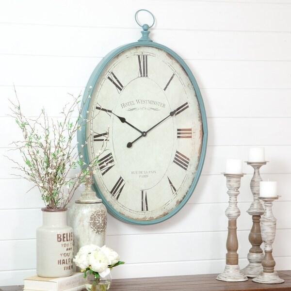 "Sonia Blue Metal Oval Wall Clock - 37.5""H x 23.5""W x 2.5""D. Opens flyout."