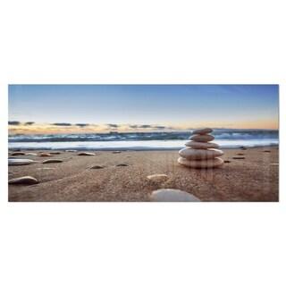 Designart 'Stones Balance on Sandy Beach' Photography Seashore Metal Wall Art Print