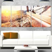 Designart 'Yacht Sailing against Sunset' Large Seashore Glossy Metal Wall Art