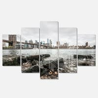 Designart 'Brooklyn Bridge with Rocks on Shore' Large Cityscape Glossy Metal Wall Art