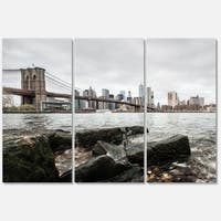 Designart 'Brooklyn Bridge with Rocks on Shore' Large Cityscape Glossy Metal Wall Art