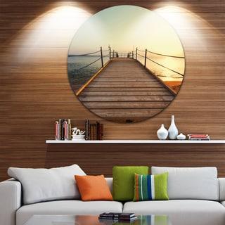 Designart 'Strong Wooden Boardwalk into Sea' Sea Bridge Round Metal Wall Art