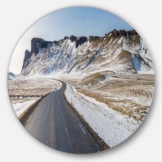 Designart 'Range Road in Winter Mountains' Landscape Round Metal Wall Art