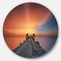 Designart 'Wooden Bridge under Illuminated Sky' Sea Pier and Bridge Large Disc Metal Wall art