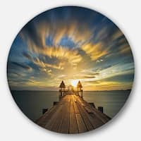 Designart 'Wooden Bridge under Dramatic Sky' Sea Pier and Bridge Disc Metal Wall Art