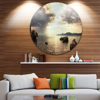Designart 'Rocky Seashore under Clouds Panorama' Modern Beach Disc Metal Wall Art