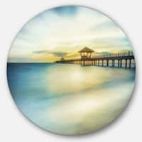 Designart 'Blue Tinged Seashore with Distant Pier' Sea Pier Circle Wall Art