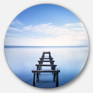 Designart 'Jetty Remains in Blue Lake' Seascape Photo Round Metal Wall Art