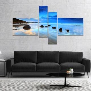 Designart 'Moeraki Boulders Under Cloudy Sky' Seashore Photo Canvas Print